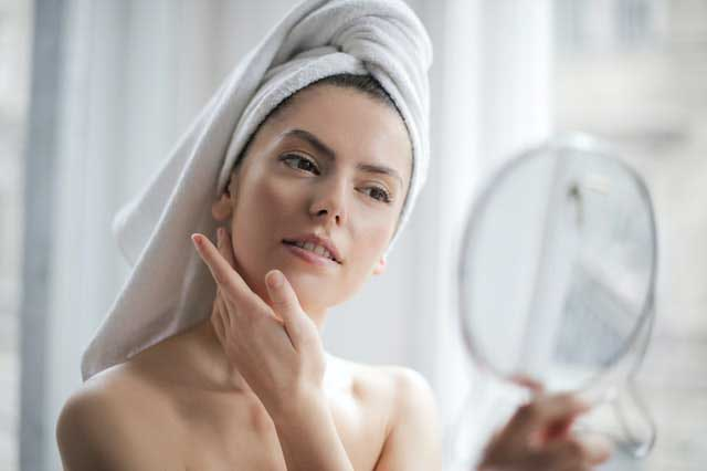 selective focus portrait photo of woman with a towel on head 3764013